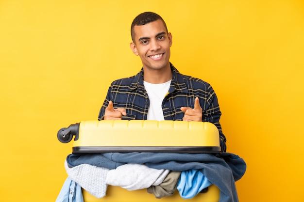 Homme voyageur avec une valise pleine de vêtements sur le mur jaune isolé pointe le doigt vers vous