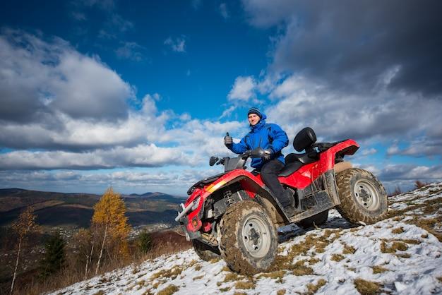 Homme sur vtt tout-terrain se reposer dans les montagnes et montrant le pouce vers le haut