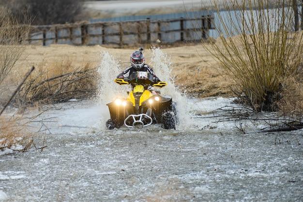 L'homme Sur Le Vtt Traverse Un Ruisseau. Balades Touristiques Sur Un Terrain De Ski De Fond. Photo Premium