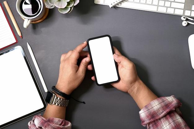 Homme de la vue de dessus à l'aide d'un smartphone mobile sur un bureau