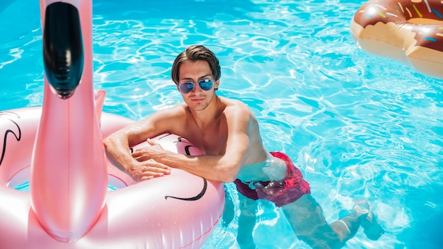 Homme vue de face sur l'anneau de bain flamant rose