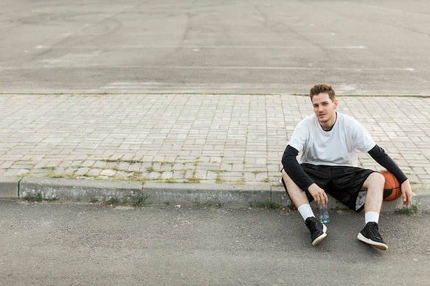 Homme vue de face, assis avec un ballon de basket