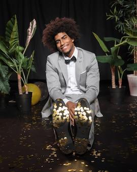 Homme de vue de face assis sur un sol entouré de confettis