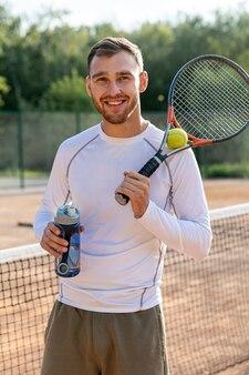 Homme vue de face hydratant sur un court de tennis