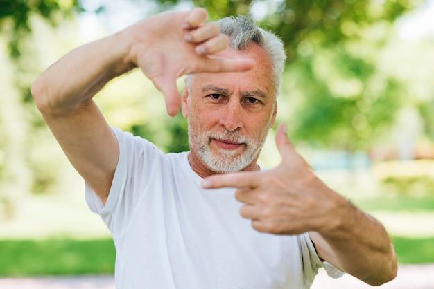 Homme vue de face montrant le geste des mains de la caméra