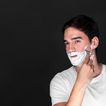 Homme vue de face rasant sa barbe