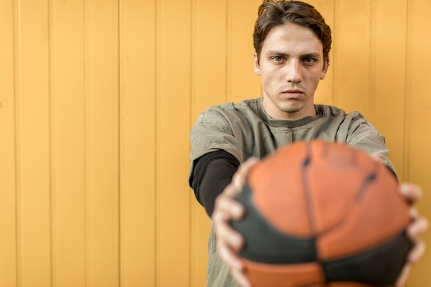 Homme vue de face tenant un ballon de basket