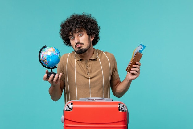Homme vue de face en vacances tenant un globe et un billet sur bleu clair
