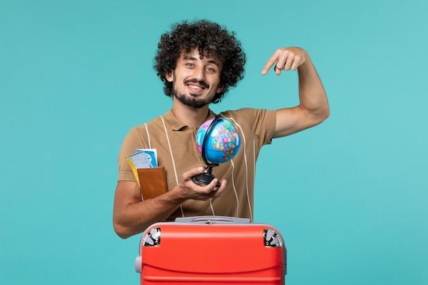 Homme vue de face en vacances tenant un globe et un billet sur bleu