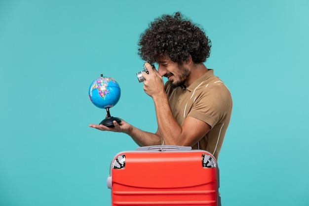 Homme vue de face en vacances tenant un petit globe et une caméra sur bleu
