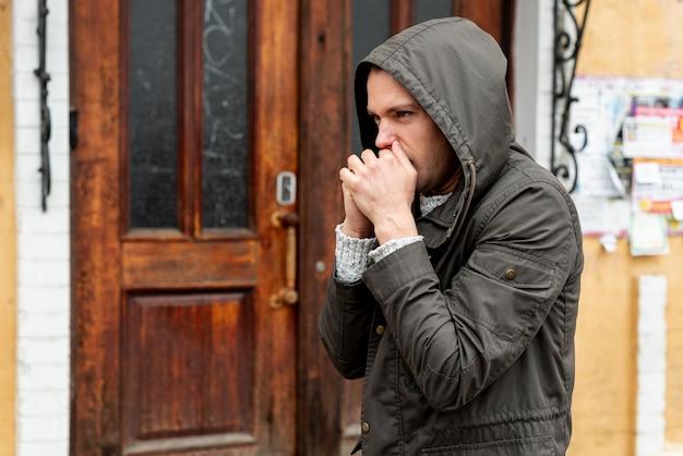 Homme vue latérale essayant de réchauffer sa main