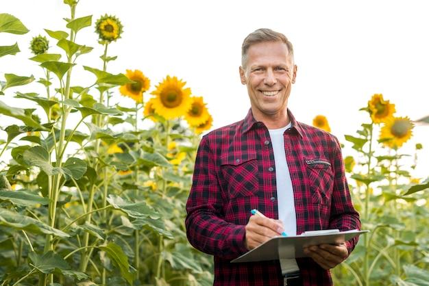Homme de vue moyenne avec un presse-papier dans un champ