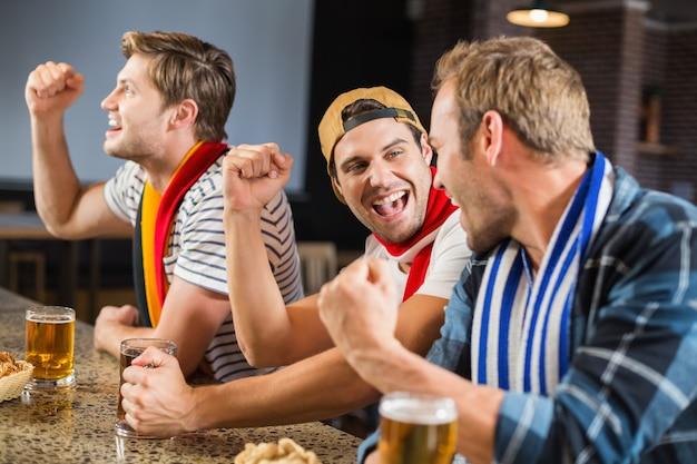 Hommes acclamant avec des bières