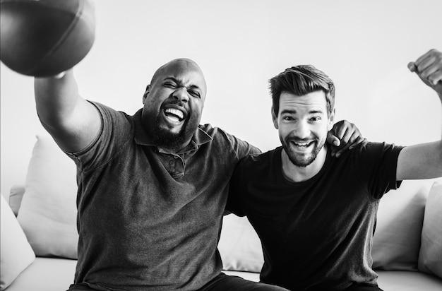 Hommes acclamant le sport ensemble
