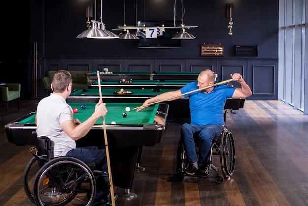 Des hommes adultes handicapés en fauteuil roulant jouent au billard dans le club