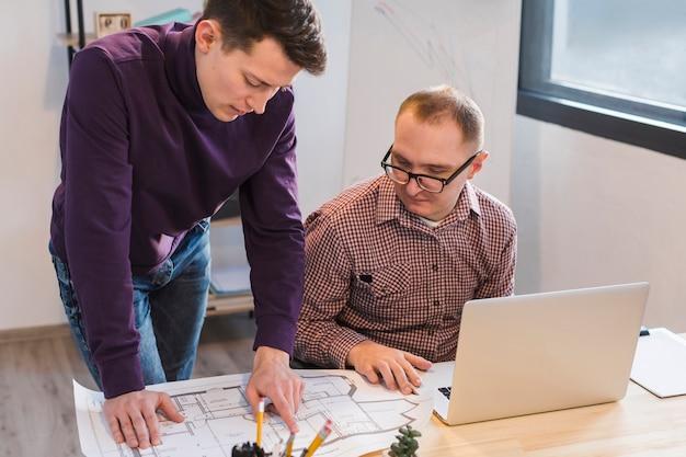 Hommes adultes travaillant ensemble sur le projet