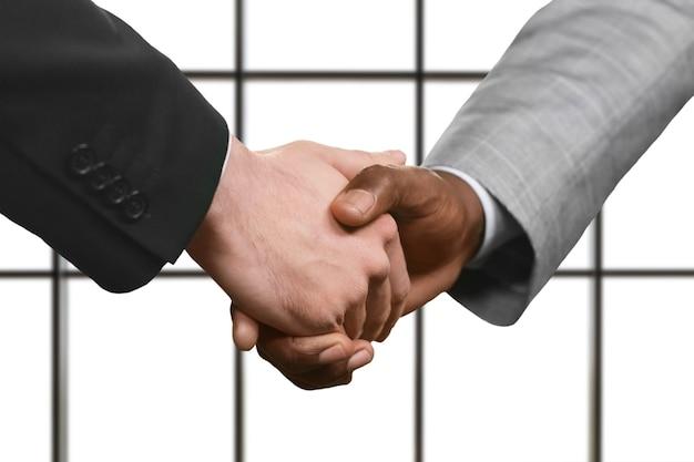 Les hommes d'affaires adultes se serrent la main. gestionnaires' poignée de main sur fond blanc. signe de respect mutuel. valorisez l'amitié.