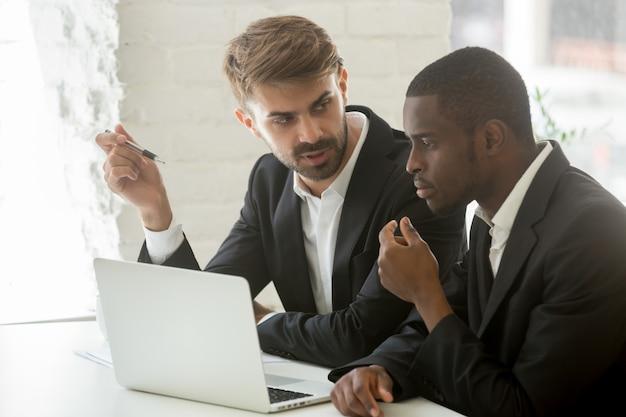 Hommes d'affaires africains et caucasiens discutant idée de projet en ligne avec ordinateur
