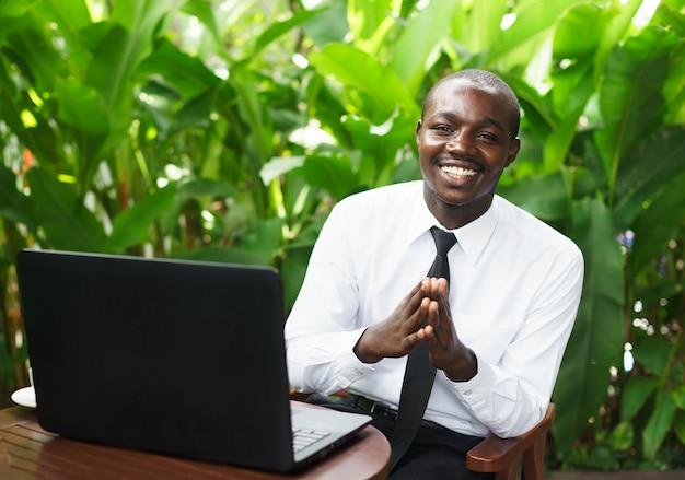 Les hommes d'affaires africains paient, plaidant et souriant joyeusement avec le cahier.