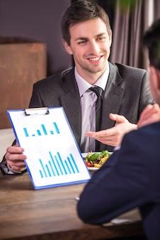 Hommes d'affaires analysant des graphiques lors d'un déjeuner d'affaires.