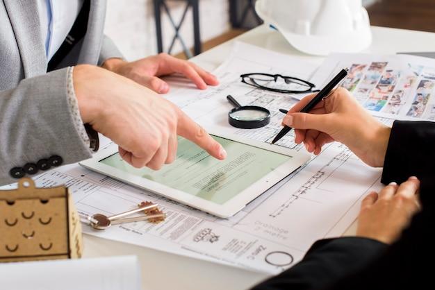 Hommes d'affaires analysant un plan d'affaires sur une tablette