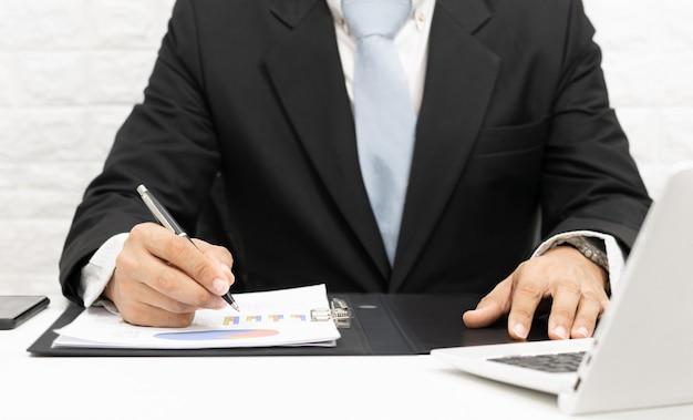 Les hommes d'affaires analysent le graphique sur le bureau