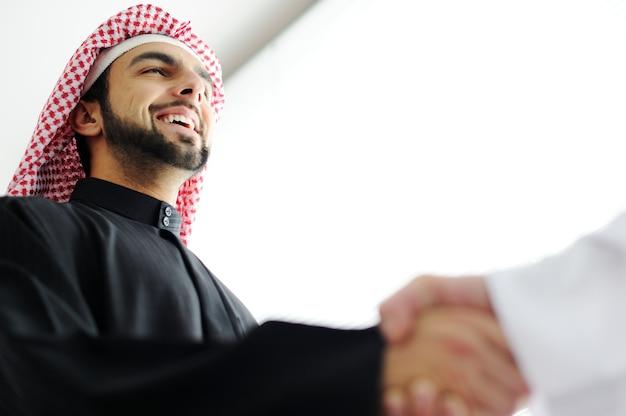 Des hommes d'affaires arabes prospères se serrant la main sur un accord