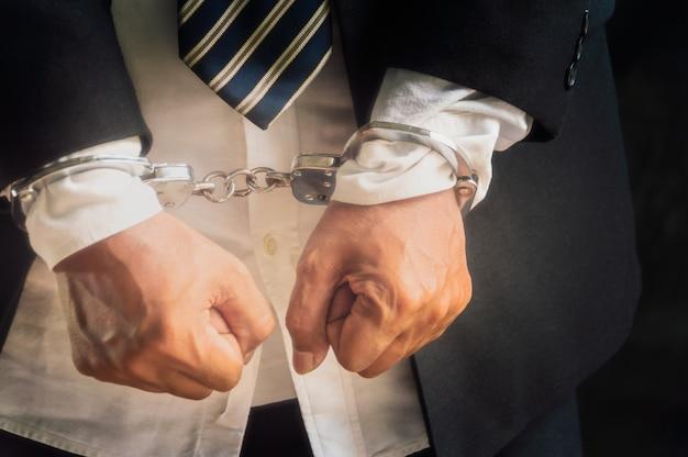 Des hommes d'affaires arrêtés et menottés
