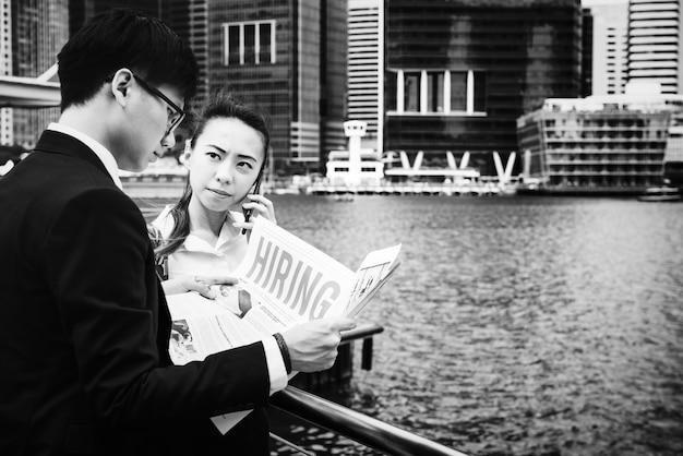 Des hommes d'affaires asiatiques dans une ville travaillant ensemble