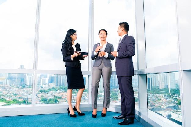 Hommes d'affaires asiatiques debout dans le bureau