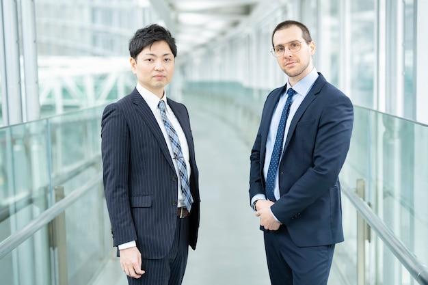 Hommes d'affaires asiatiques et européens debout au bâtiment d'entreprise