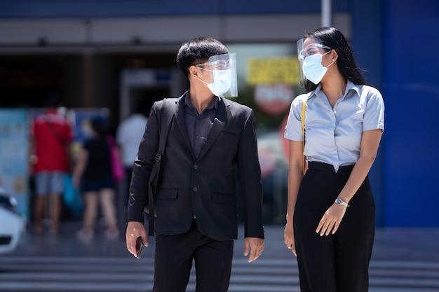 Les hommes d'affaires asiatiques parlent à distance, ils portent un écran facial.