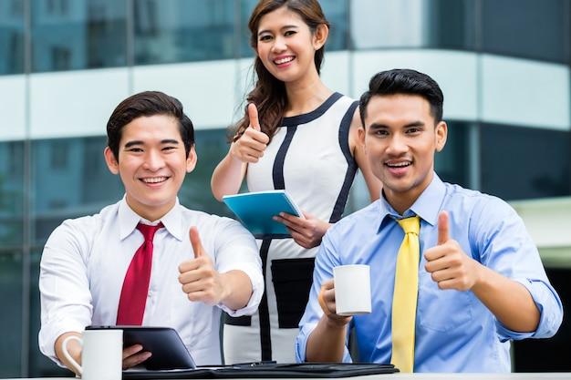 Hommes d'affaires asiatiques travaillant à l'extérieur avec du café