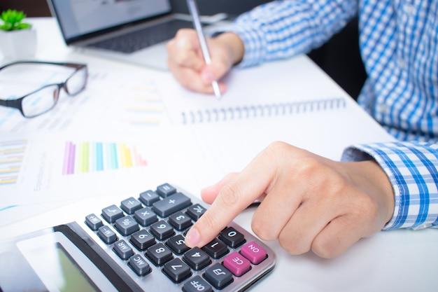 Des hommes d'affaires asiatiques utilisant une calculatrice pour représenter graphiquement les tableaux financiers sur le bureau blanc.