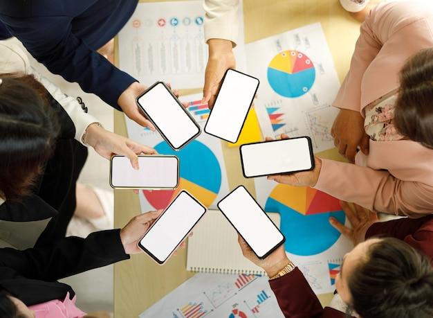 Des hommes d'affaires assis ensemble au bureau sur un bureau avec un graphique coloré et des graphiques pater, tiennent des smartphones dans un modèle différent avec des écrans vierges. prise de l'angle de vue de dessus.