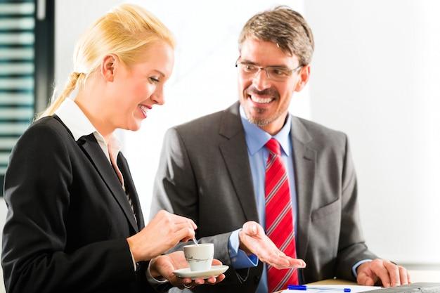 Hommes d'affaires au bureau d'affaires boivent du café