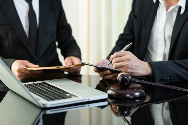 Hommes d'affaires et avocats discutant des documents contractuels assis à la table. notions de droit, conseils, services juridiques. à la lumière du matin