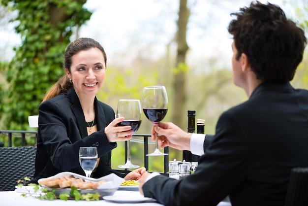 Les hommes d'affaires ayant un déjeuner d'affaires à l'extérieur sur la terrasse dans un restaurant gastronomique