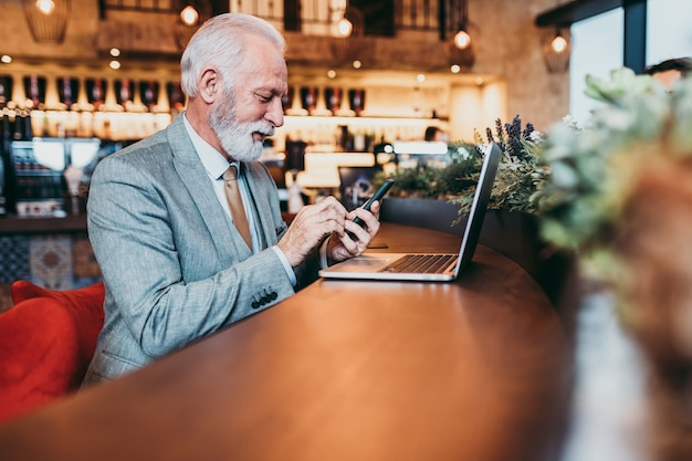 Hommes d'affaires de barbe mature travaillant sur ordinateur portable dans un café moderne.