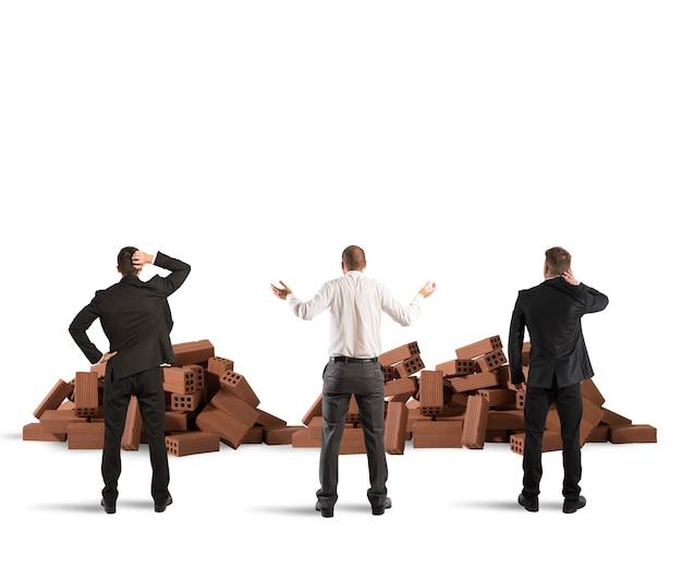 Les hommes d'affaires confus regardent une brique de construction brisée