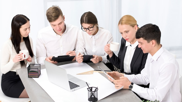 Hommes d'affaires créatifs avec mobile; ordinateur portable et tablette numérique travaillant ensemble au bureau