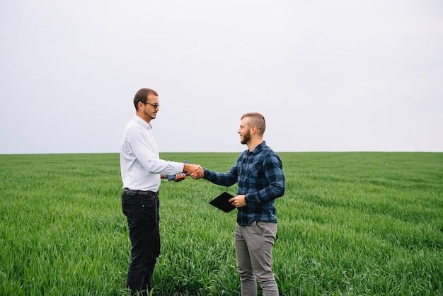 Hommes d & # 39; affaires debout dans un champ de blé avec tablette