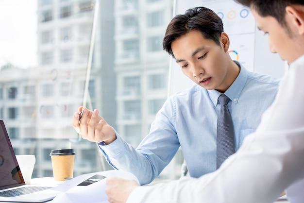 Hommes d'affaires discutant de documents dans une salle de réunion dans un bureau moderne