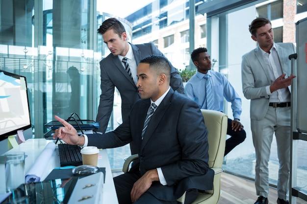 Hommes d'affaires discutant à table sur ordinateur