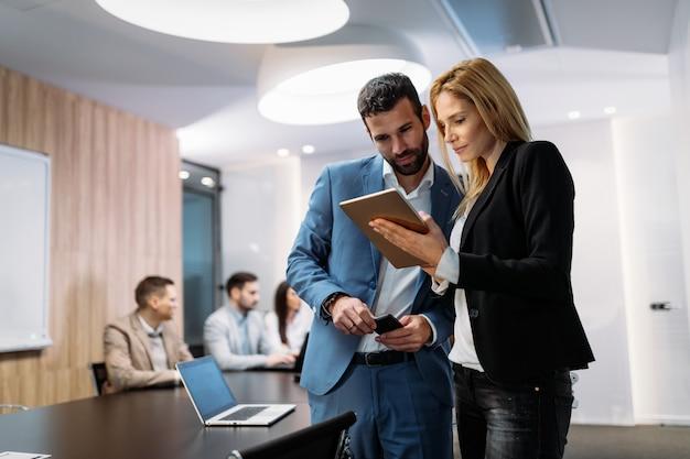 Hommes d'affaires discutant tout en utilisant une tablette numérique au bureau ensemble