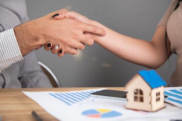 Les hommes d'affaires discutent des horaires et de la maison. serrer la main