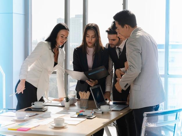 Hommes d'affaires de la diversité debout et regardant le rapport d'analyse des données financières du ducument d'assurance lors d'une réunion d'affaires au bureau, travail d'équipe concentré, analyse commerciale et concept de stratégie