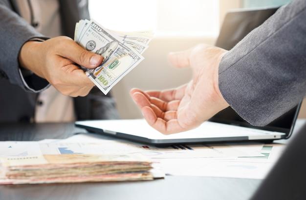 Hommes d'affaires donnant des billets en dollars
