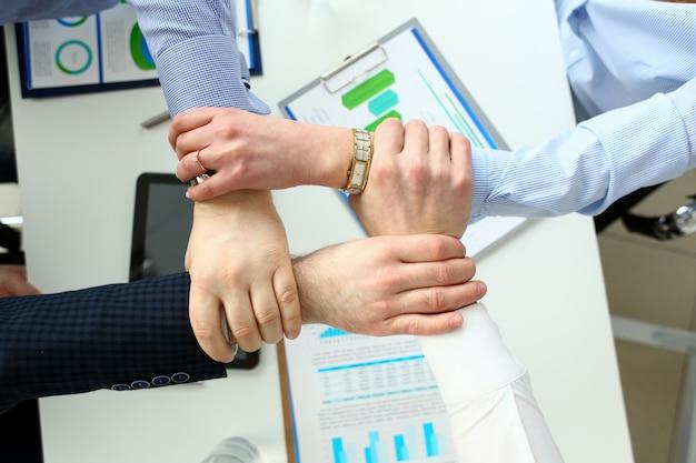 Les hommes d'affaires du groupe tiennent bras dans les serrures