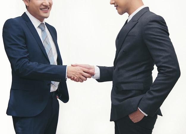 Hommes d'affaires faisant l'étiquette de poignée de main sur blanc